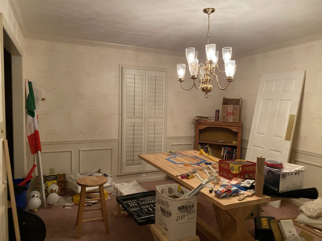 A messy dinig room full of all kinds of renovation tools with a dated light fixture and a Settlers of Catan board game set up on the table.