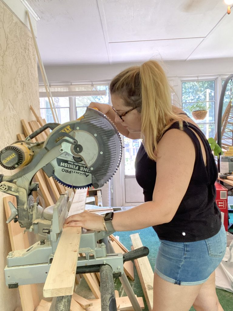 This is a picture of me wearing a black shirt and jean shorts with my long blonde hair in a pony tail in my work room using a miter saw to cut a 1 by 3 piece of wood.