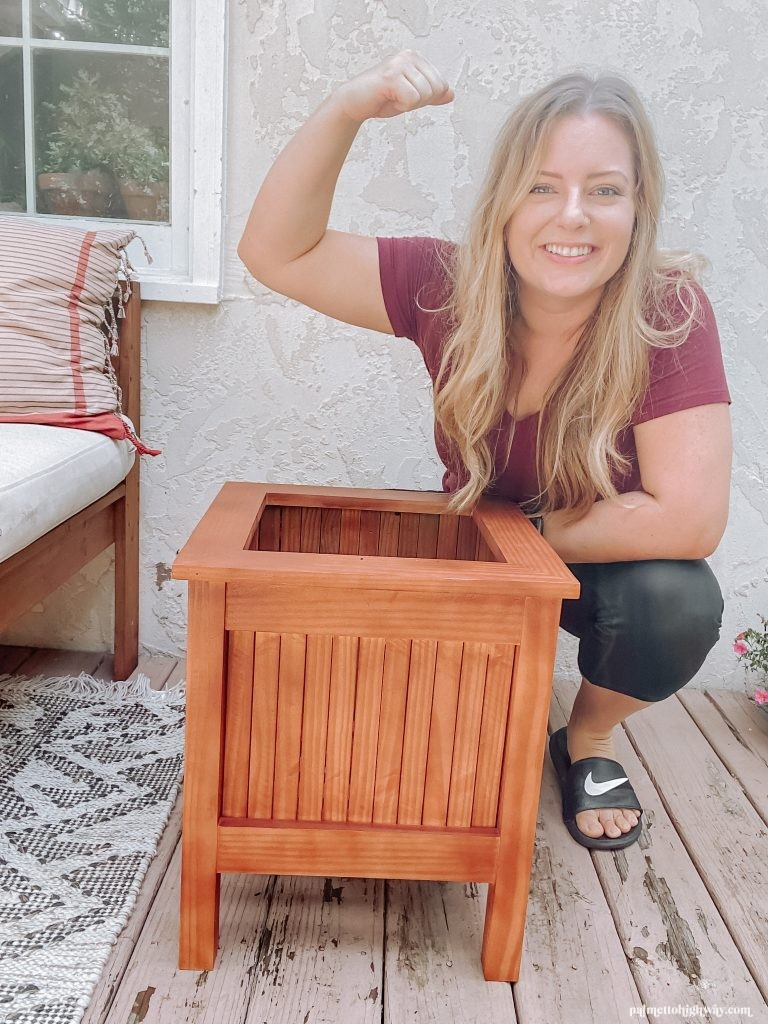 This is an image of me crouching behind the planter. I am holding my arm up as if I am showing off my arm muscles The planter has some red wood tones. It is square in shape and does not have a plant in it.