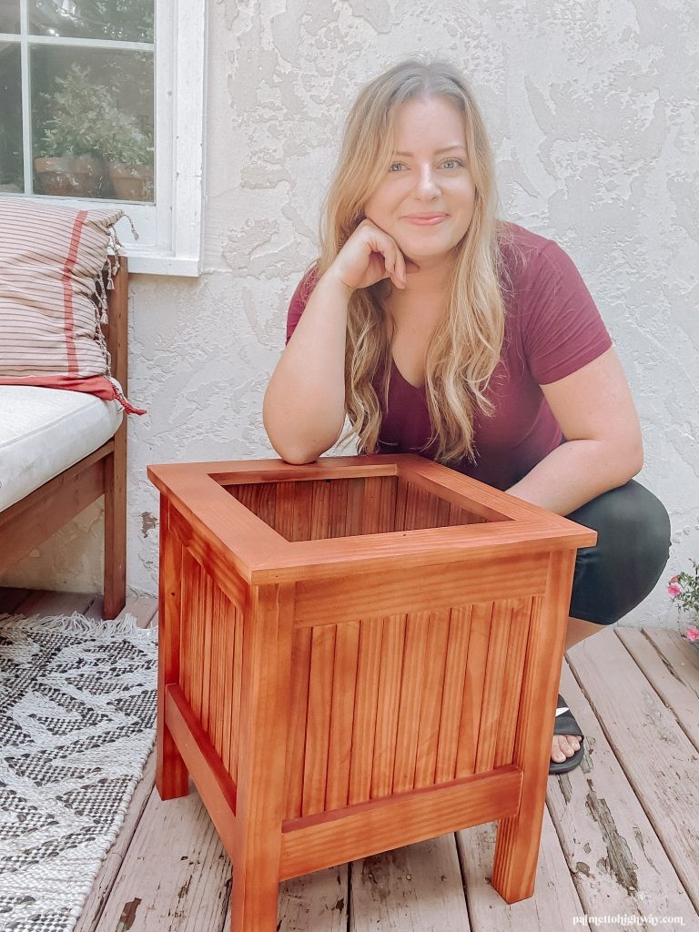 This is an image of me crouching behind the planter. The planter has some red wood tones. It is square in shape and does not have a plant in it.