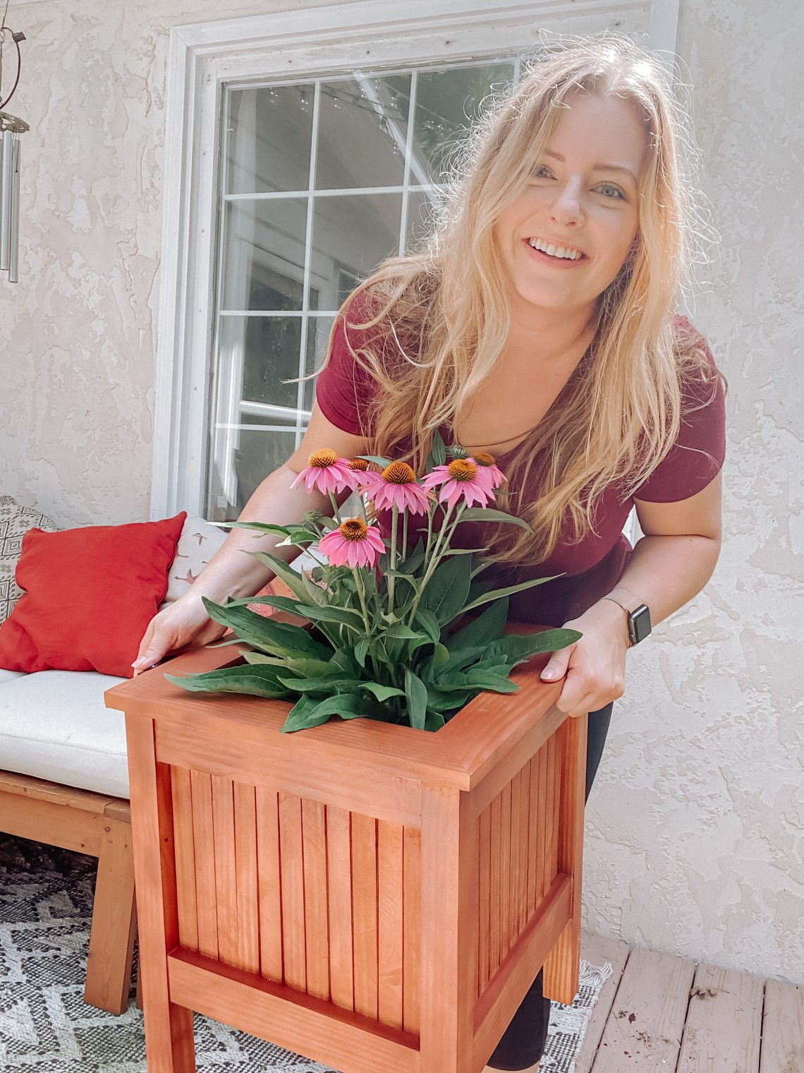 I'm holding the planter. It is square with a brown/red stain. There are pink flowers in it.