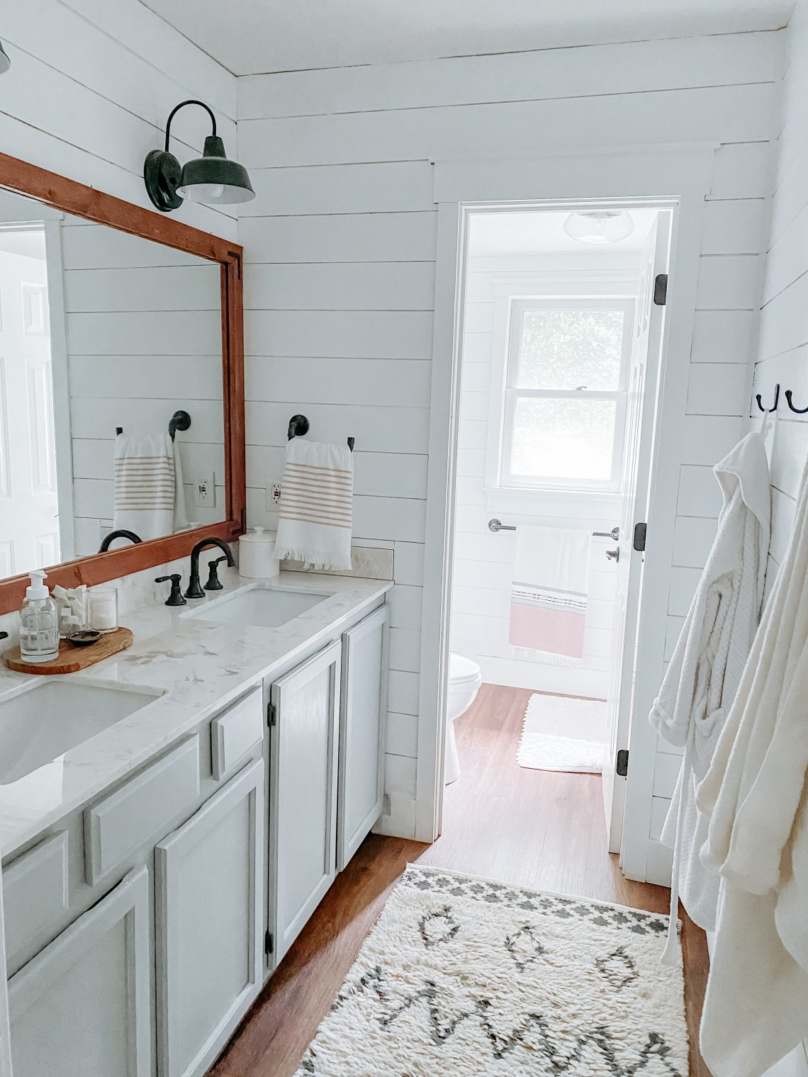 A completed bathroom with bright light, white shiplap walls, light colored counters, bronze hardware, and warm wood floors.