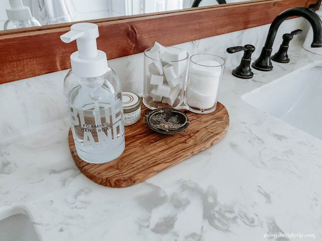 Couter top functional accessories on a wood tray. There is a soap dispenser, candle, jewelry tray, and makeup sponges.