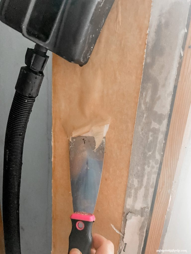 Steaming wallpaper with the steamer above and scraping with a paint scraper below