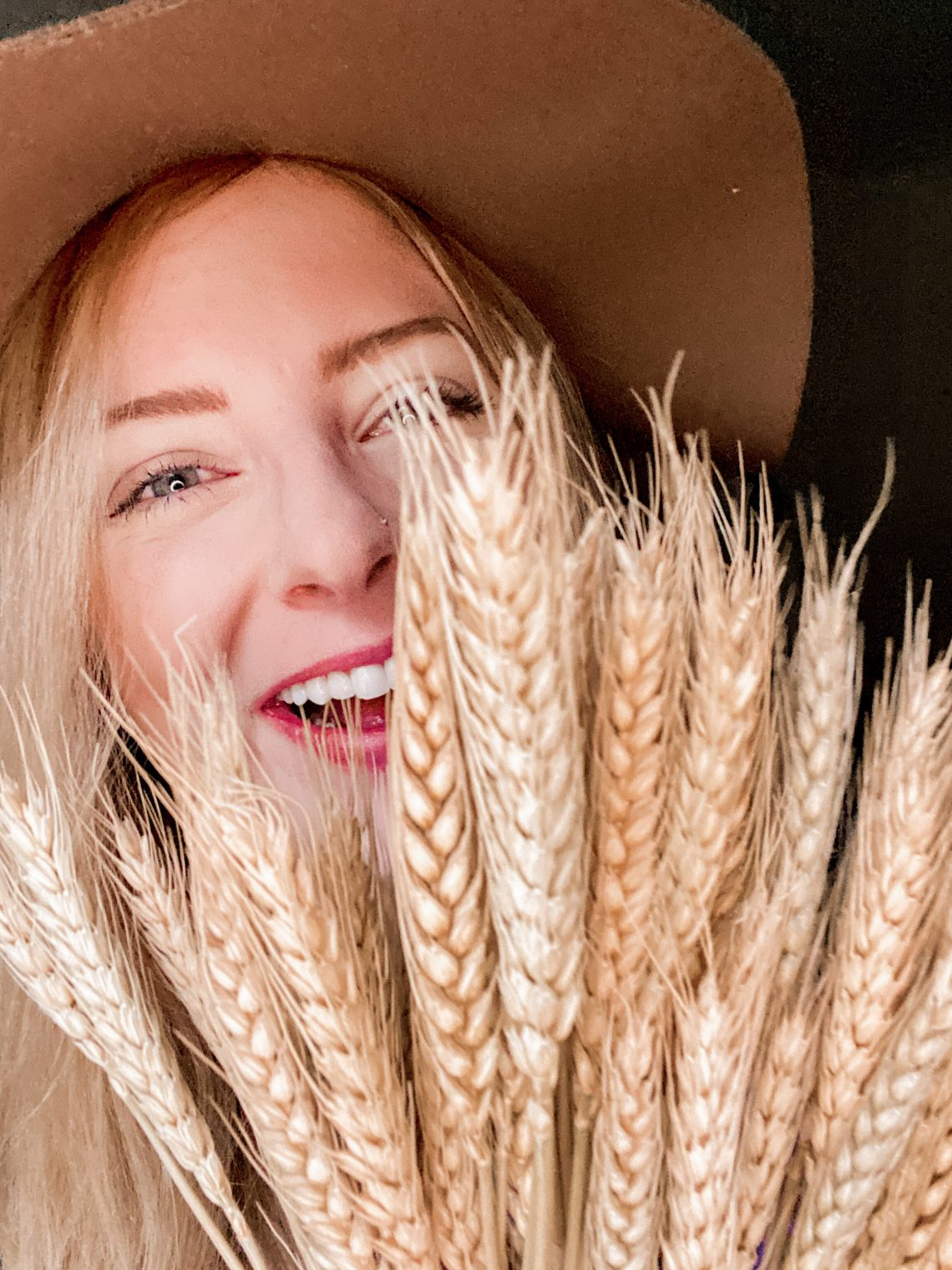 I am smiling behind dried wheat