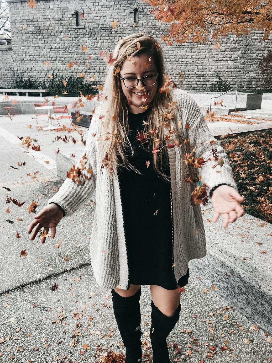 Its fall and I had tossed fallen leaves and they are falling on me and I am smiling wearing a white dress, black boots, and grey sweater