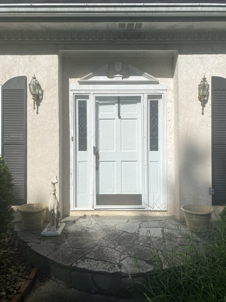 The before image of my entryway. The door is bright white, there are two dated lanterns in brass on either side and black shutters.