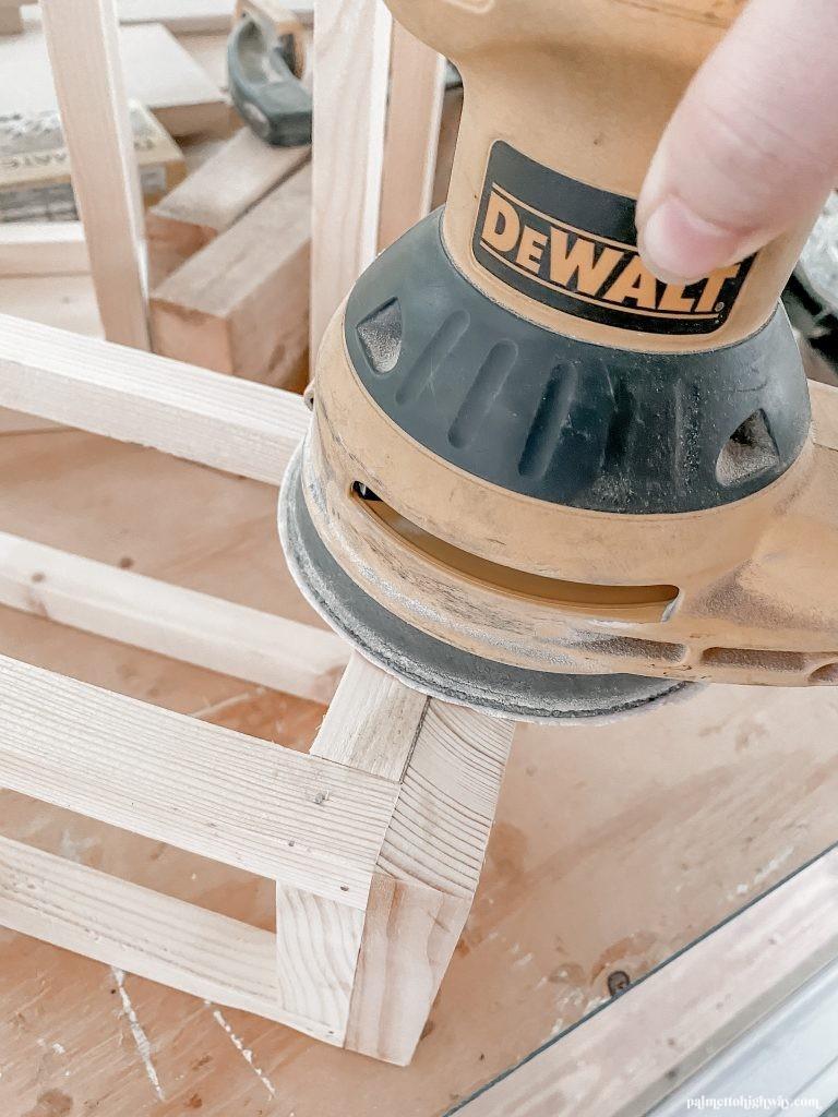 DeWalt orbital sander smoothing out the unfinished wood on the lanterns