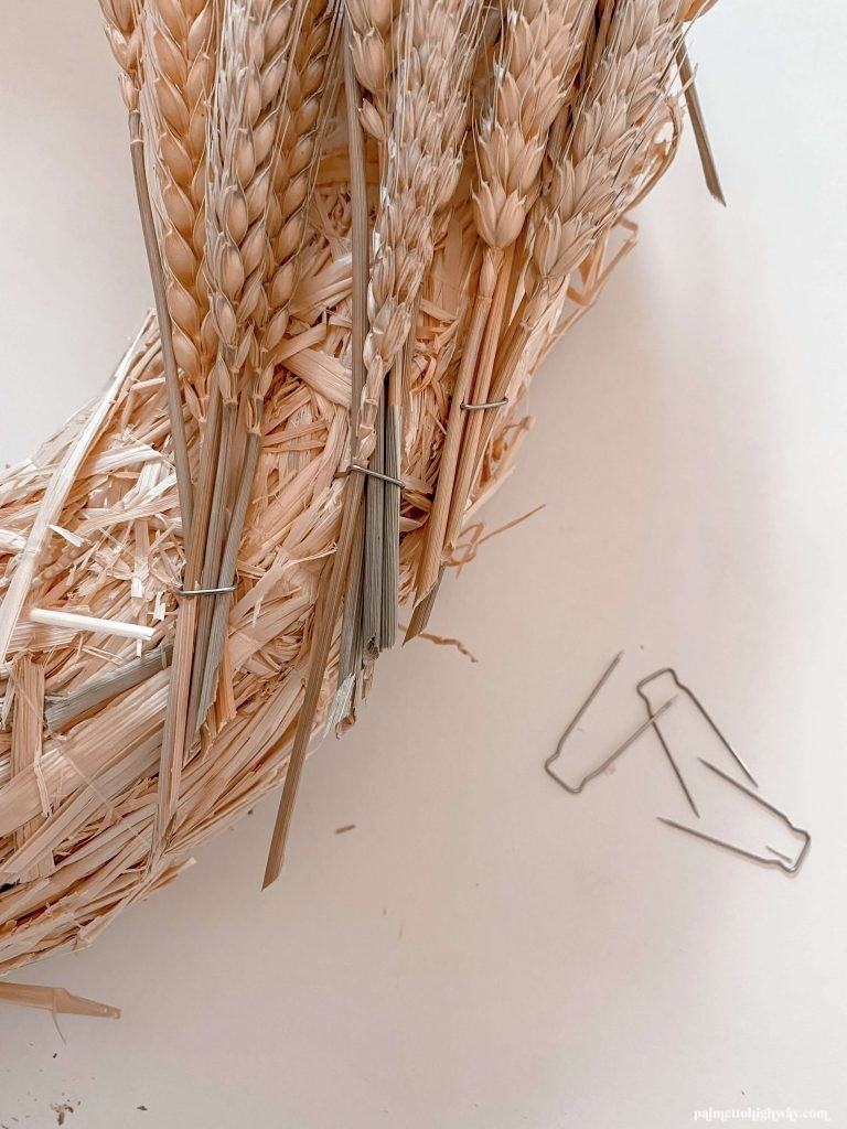 Bundles of wheat are pinned down using tidy pins and can be seen pinned to the straw wreath base