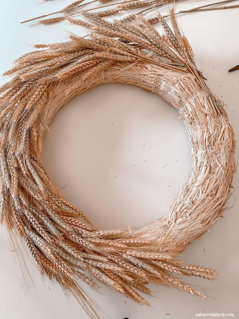 Half the straw wreath base has dried wheat applied to it. The wreath is not completed.