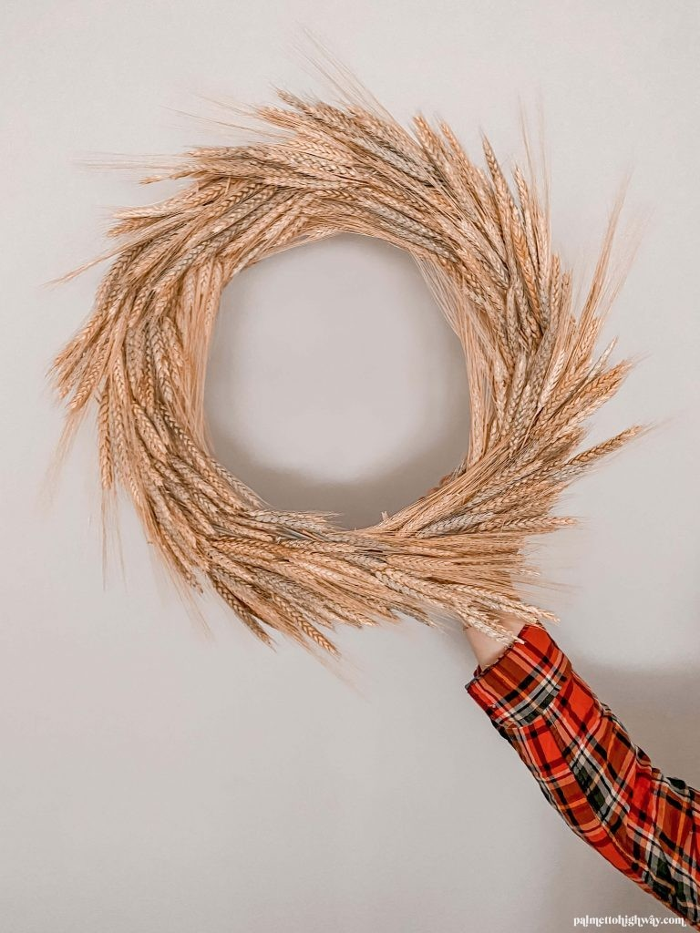 Completed wheat wreath held against a blank wall