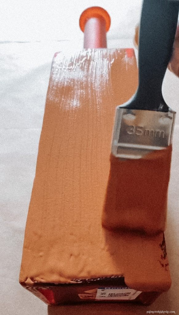 A vase is being painted a rust color with a paint brush.