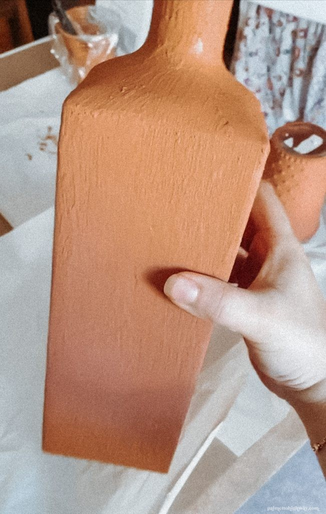 A vase fully painted being held up close to show texture.