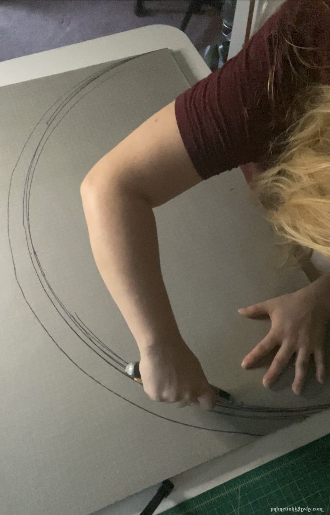Multiple wobbly half-circles are drawn on the backside of a doormat and a girl is cutting with a box cutter.