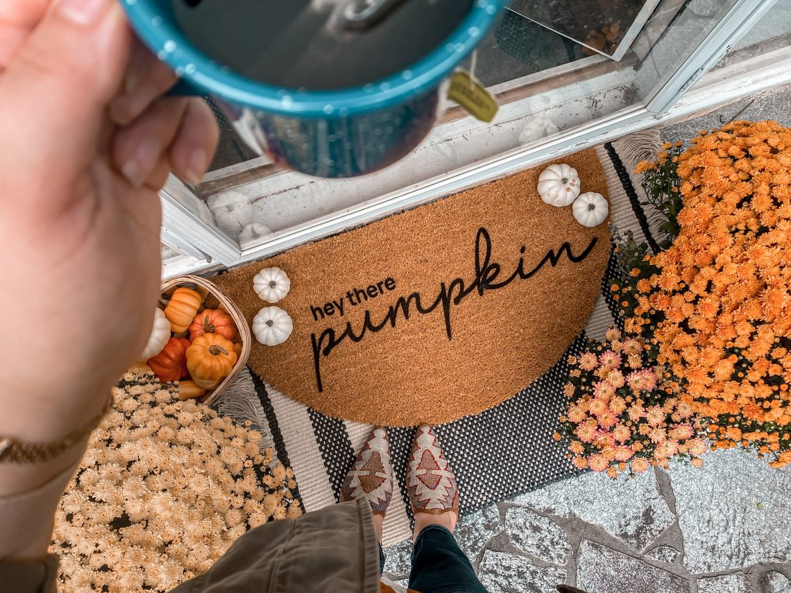 "A half-circle doormat down below says ""hey there pumpkin"". There are yellow and orange mums off to the side and small pumpkins on the mat. There is a blue cup of tea, blurred out in the foreground."