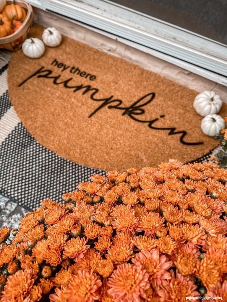 """Close up image showing orange mum flower and a half circle coir doormat with the words """"hey there pumpkin"""""""
