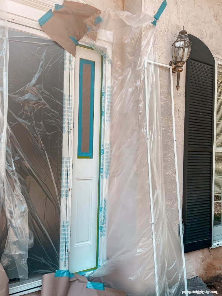 The side panels next to the door are taped and the surrounding area covered in plastic.