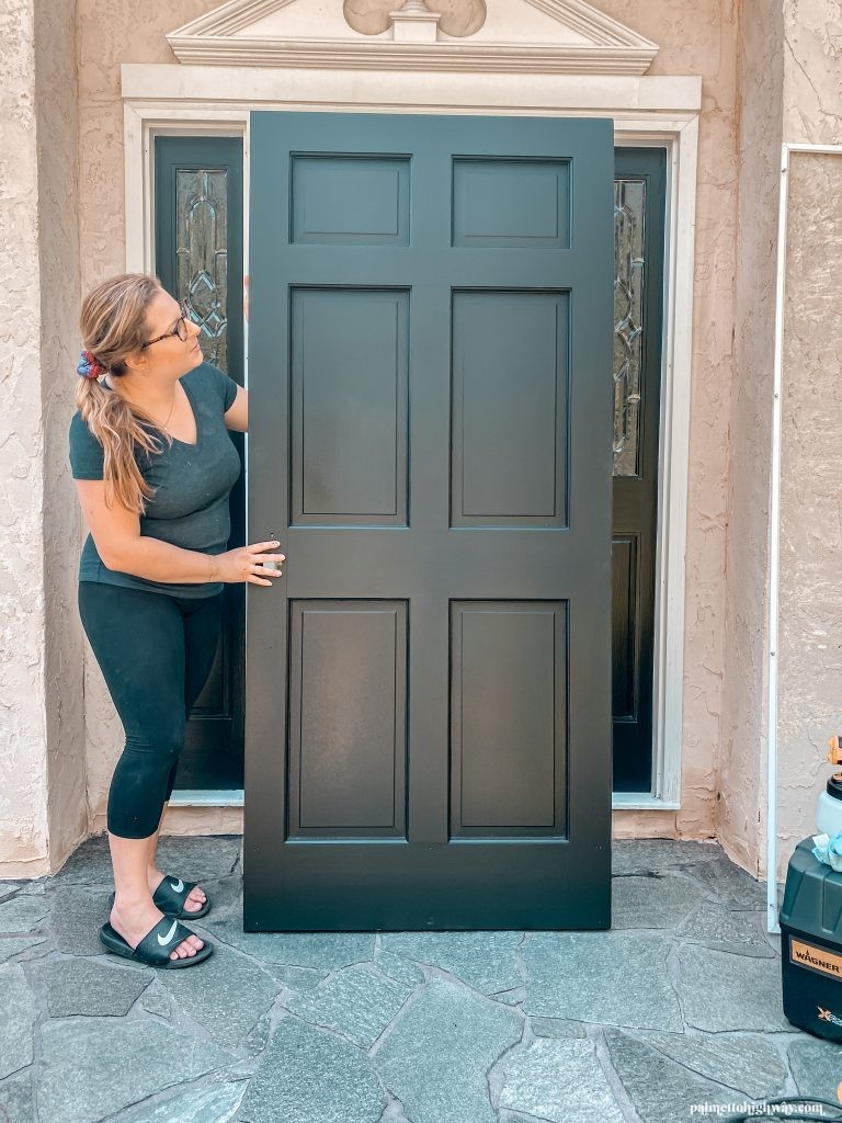 A girl is in front of a house holding up a black door