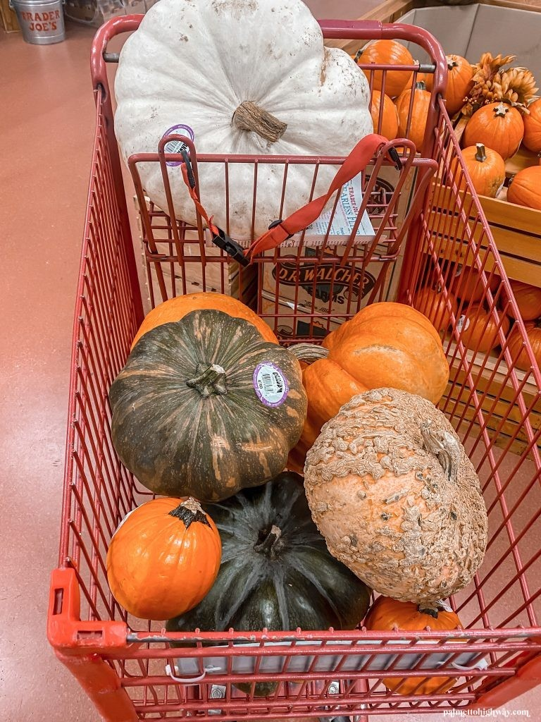 This is a red Trader Joes shopping cart filled with fun shaped and colorful pumpkins