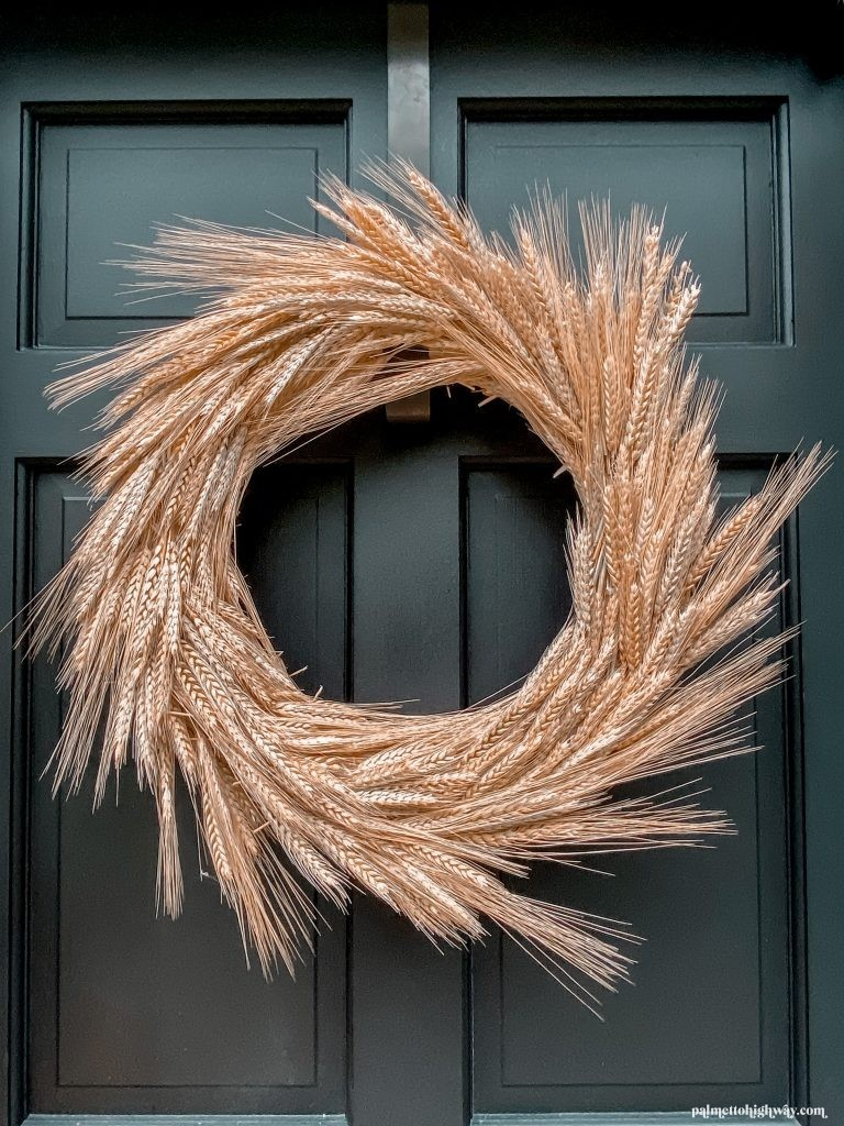 A dried wheat wreath hangs on a black door