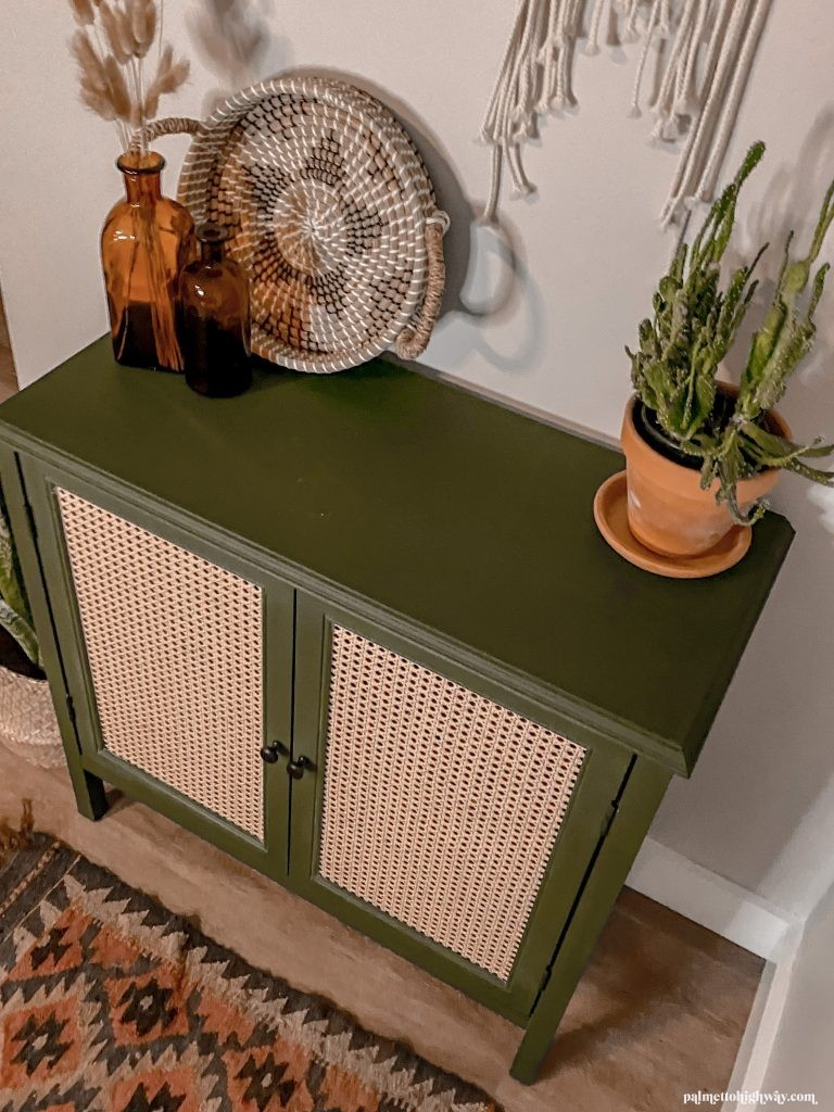 Completed green cabinet with caning on the cabinet doors. The cabinet is styled with plants and amber glasses.