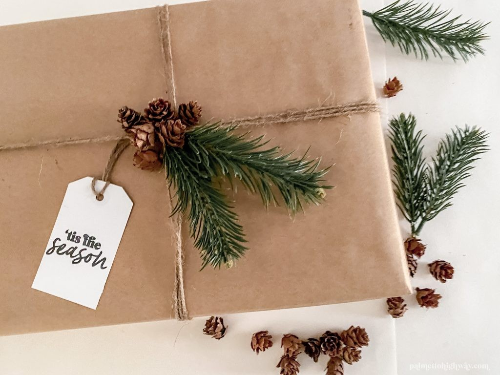 Gift wrapping example with tiny pine cones and faux pine sprigs