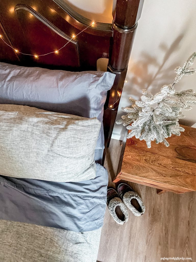 Blue/Gray sheets on a bed with gray duvet, dark wood headboard and a decorative christmas tree on the side table
