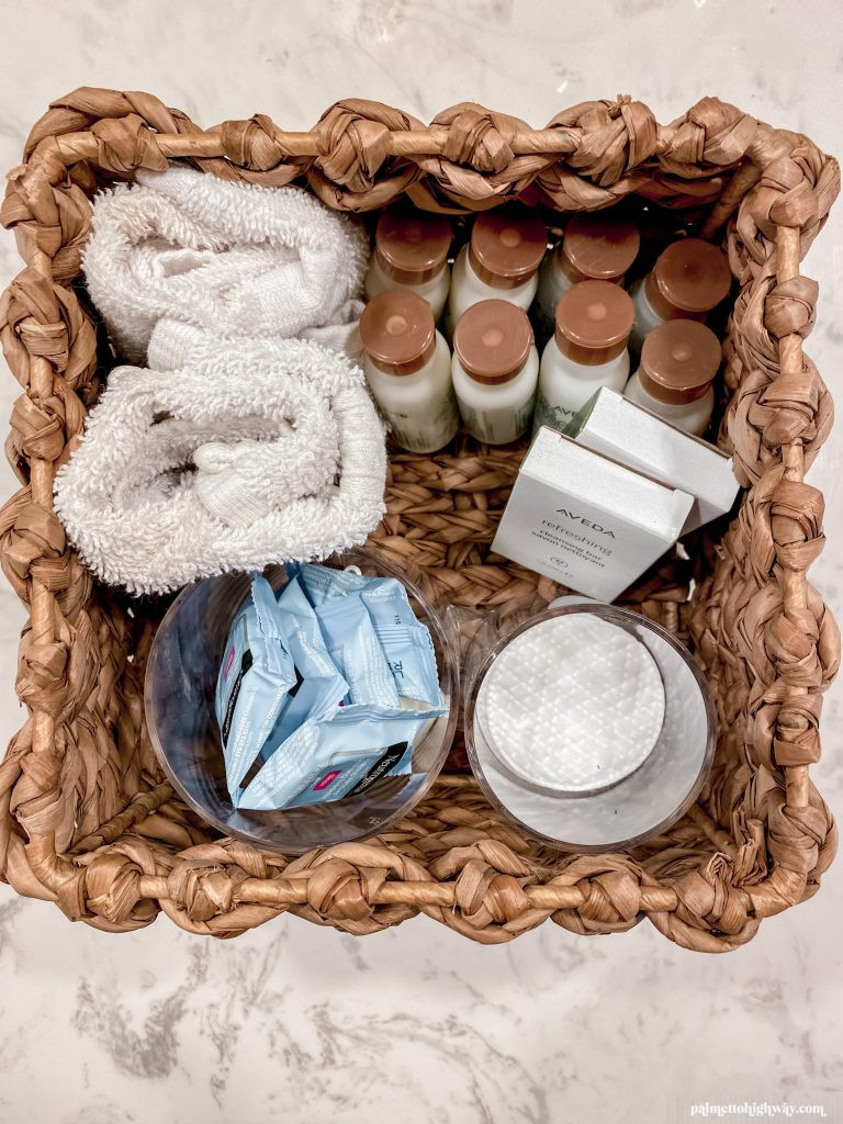 A look from above down into a basket with some small towels and back up soaps and shampoo/conditioner. This is backstock to prepare for holiday guests