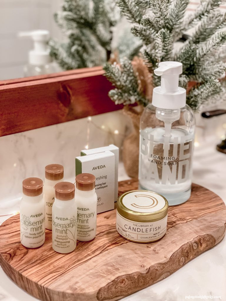 Mini shampoo and conditioners on a wood tray next to hand soap, a candle, and a small decorative christmas tree