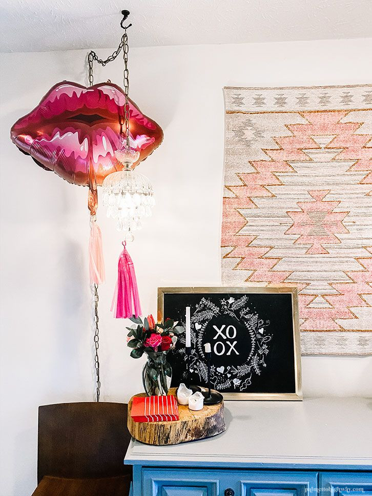 Valentines decor. There is a pink southwestern pattern on a tapestry, lip shaped balloon, a small plant and a chalk board that says 'xoxo'.
